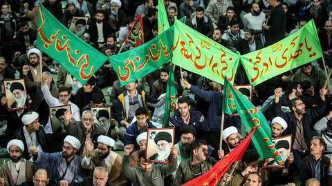 En gruppe iranere marsjerer i støtte for regjeringen etter at det siden torsdag har vært store protester mot regjeringen.