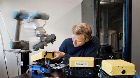 Sintef har utviklet teknologi som får roboter til å unngå kollisjon med andre gjenstander og mennesker – ikke ved å stoppe, men ved å gå rundt hinderet. Her viser forsker Øystein Hov Holhjem hvordan slik teknologi åpner for effektivt samspill mellom roboter og mennesker.