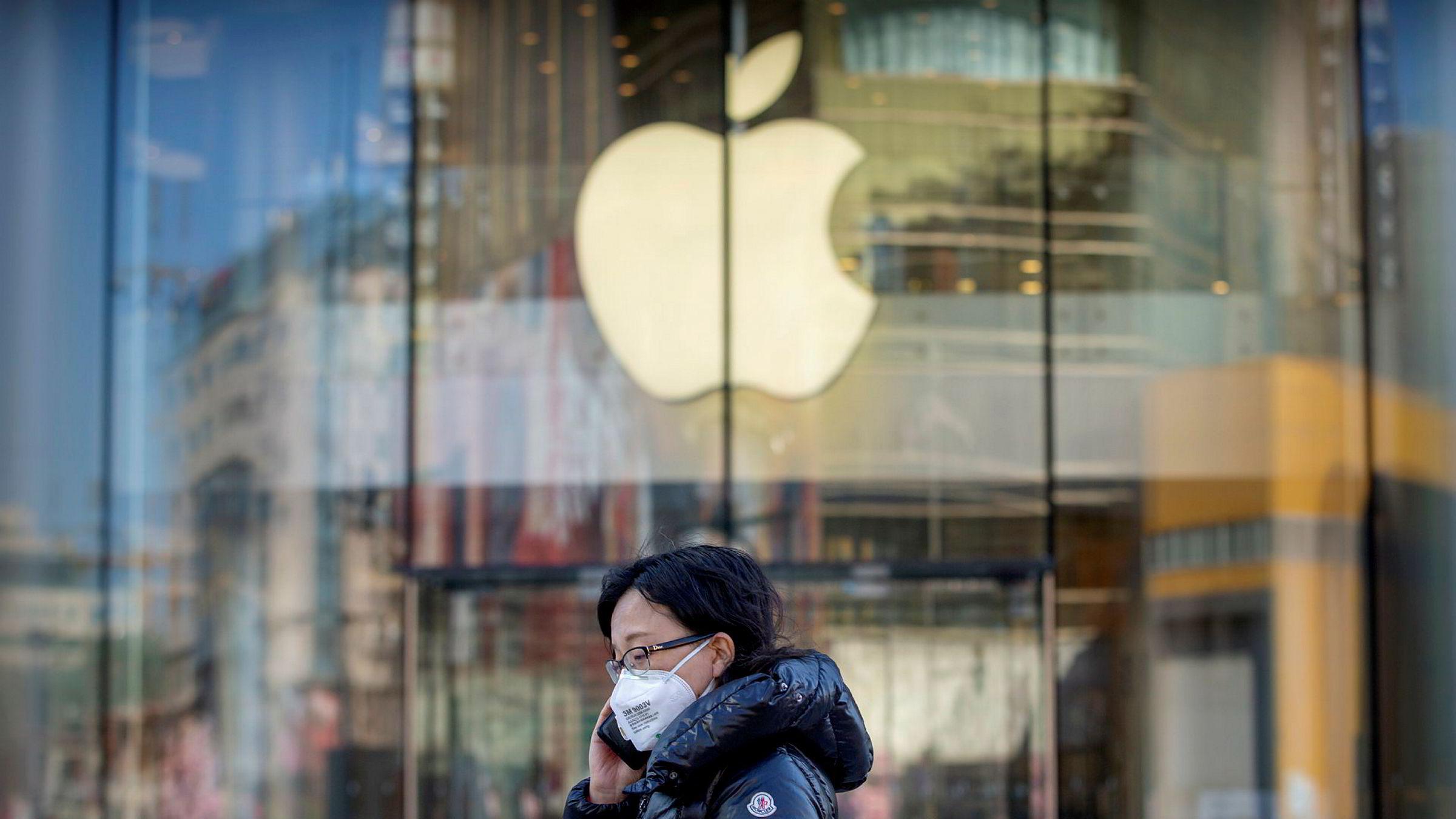 En kvinne med ansiktsmaske passerer en av Beijings Apple-butikker. De er midlertidig stengt på grunn av virusutbruddet.