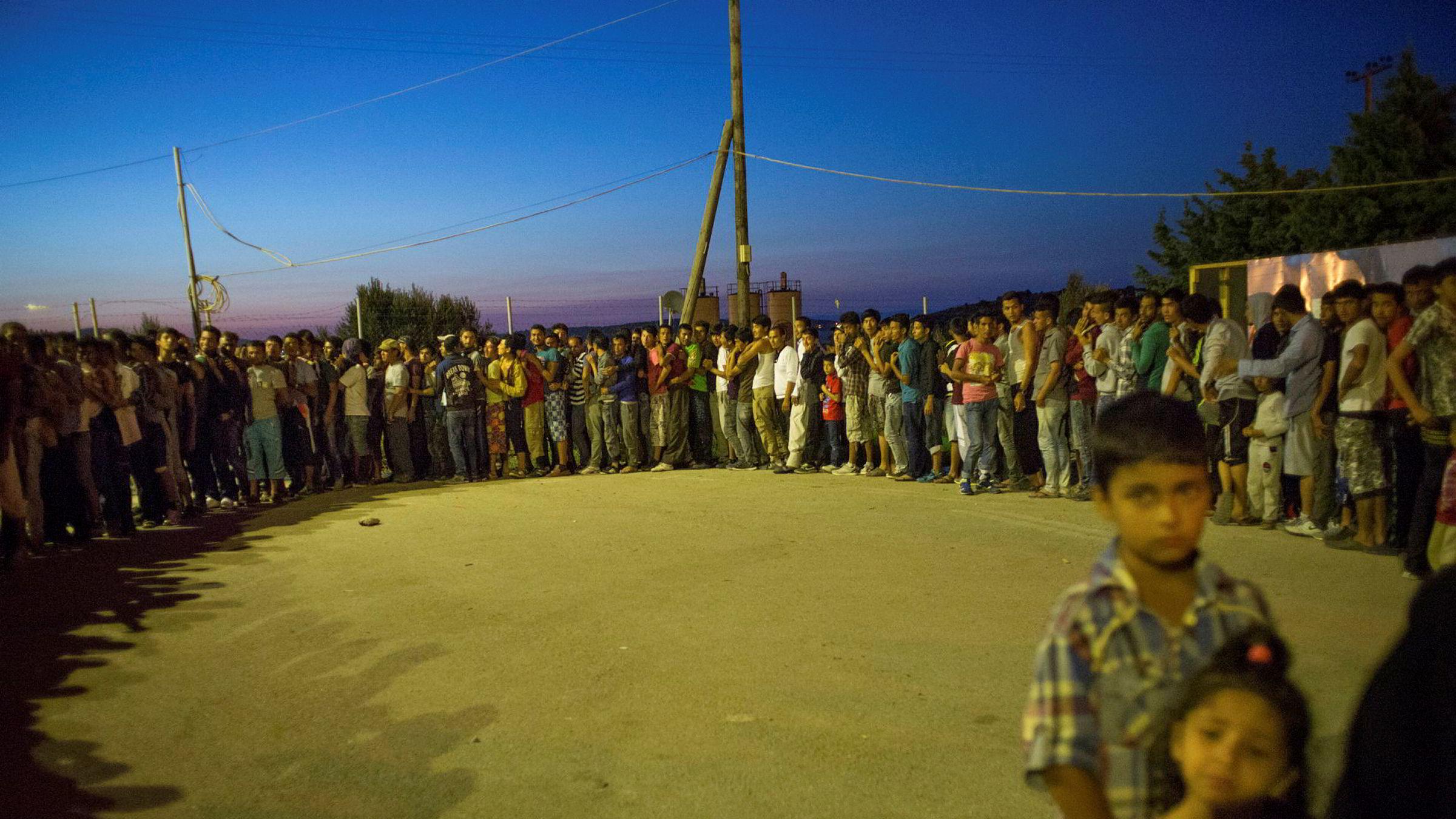 Flyktninger fra hovedsakelig Afghanistan køer opp foran varebilene med mat i flyktningleiren i Kara Tepe i Lesbos i 2015. I leiren finnes det egne områder for levering av mat til barn og kvinner.