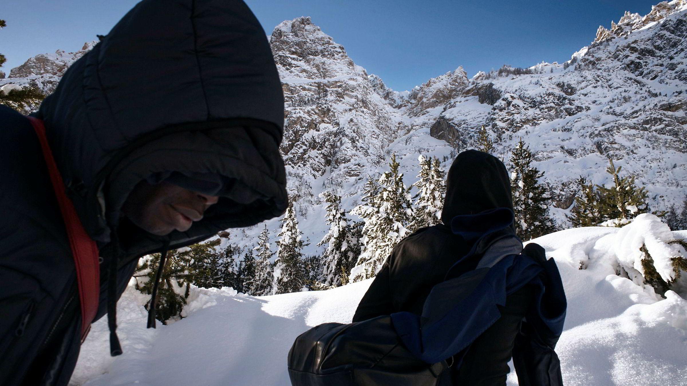 Innvandring er et hett tema i Italia før søndagens valg. Ikke alle ser for seg en fremtid i Italia, som disse to som har valgt å gå over Alpene ved fjellpasset Colle della Scala for å komme seg videre inn i Frankrike. Bildet er tatt i januar.