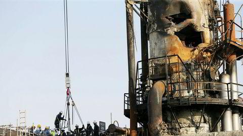 Arbeidere fikser en ødelagt plattform i Abqaiq, Saudi Arabia.