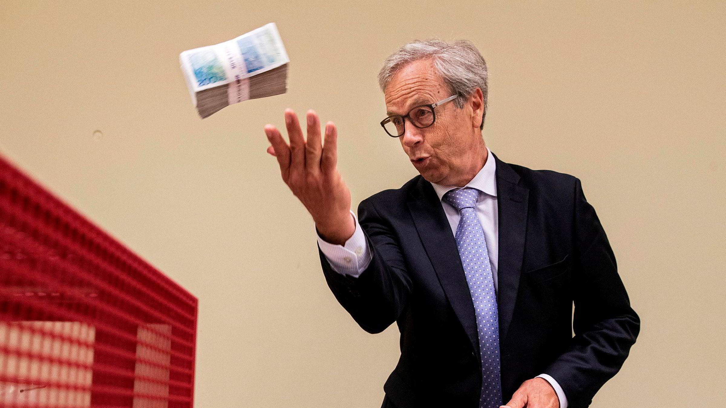 Sentralbanksjef Øystein Olsen kaster en bunke med gamle 200-kronesedler. Bildet er fra tidligere i år i forbindelse med at de gamle 100- og 200-kronesedlene ikke lenger er gyldig som betalingsmiddel.
