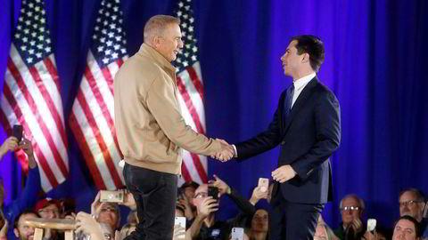 Presidentkandidat Pete Buttigieg (til høyre) hilser på skuespiller Kevin Costner under et valgkamparrangement i Indianola i Iowa søndag.