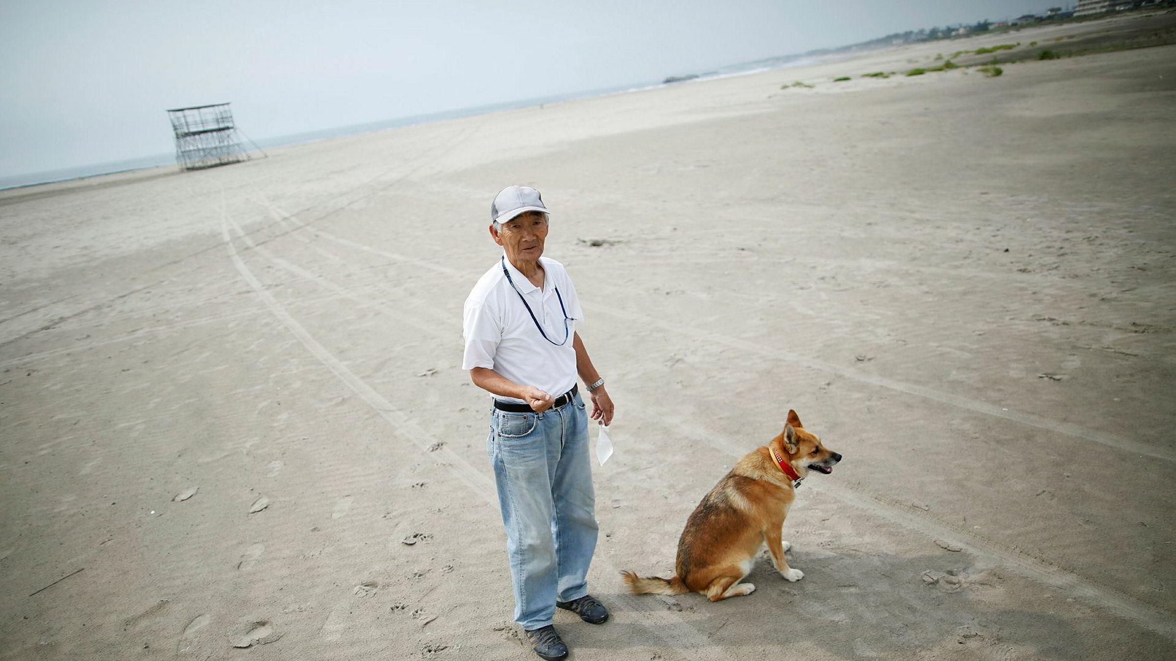 Forskere har målt høye nivåer av radioaktiv stråling på strender langt fra det ødelagte kjernekraftverket i Fukushima. På bildet ser vi lokal beboer Takeshi Takaki ( 71) og hans hund Marron på den tomme stranden Yotsukura 40 kilometer fra Fukushima. Denne stranden er ikke undersøkt av forskerne.