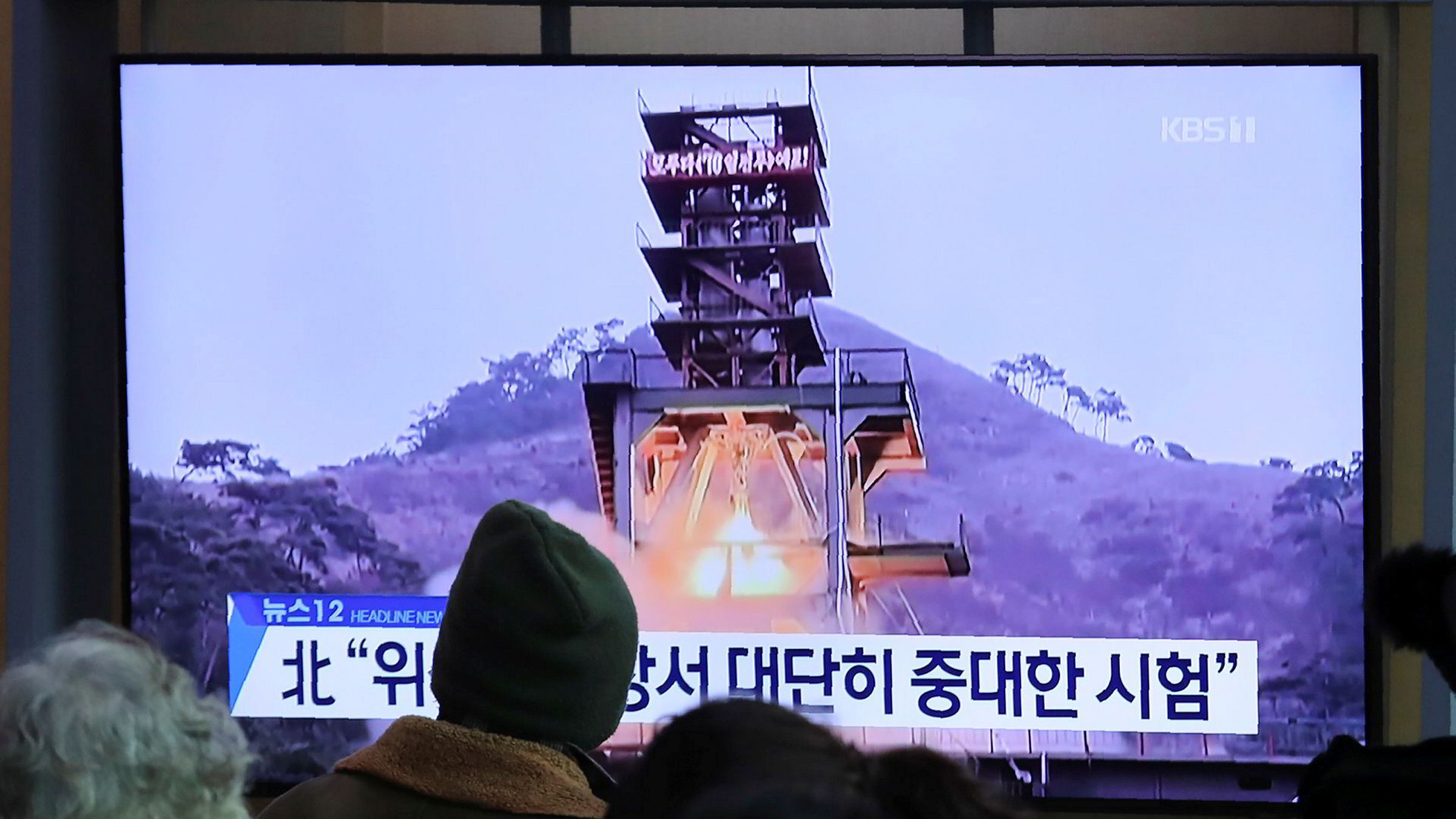 People watch a TV screen showing a file image of a ground test of North Korea's rocket engine during a news program at the Seoul Railway Station in Seoul, South Korea, Monday, Dec. 9, 2019. North Korea said Sunday it carried out a _very important test_ at its long-range rocket launch site that it reportedly rebuilt after having partially dismantled it after entering denuclearization talks with the United States last year. The sign reads: _Very important test._ (AP Photo/Ahn Young-joon)