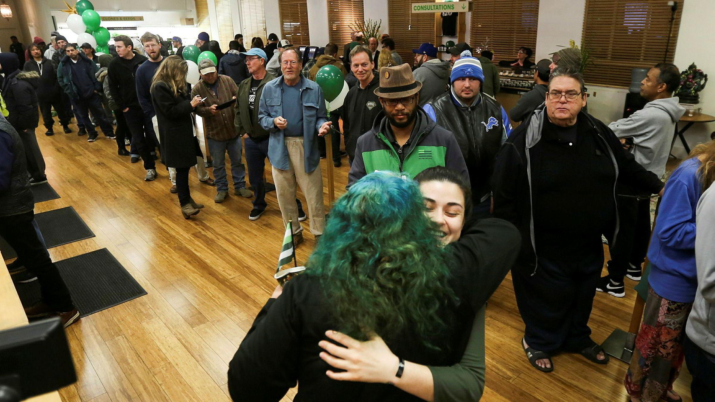 En ansatt ønsker de første kundene hjertelig velkommen til marihuanabutikken Harborside i Oakland. Frem til nå har dette tradisjonsrike utsalget kun fått selge til medisinsk bruk mot legeattest. Køene var mandag lange utenfor de fleste utsalgene i California.