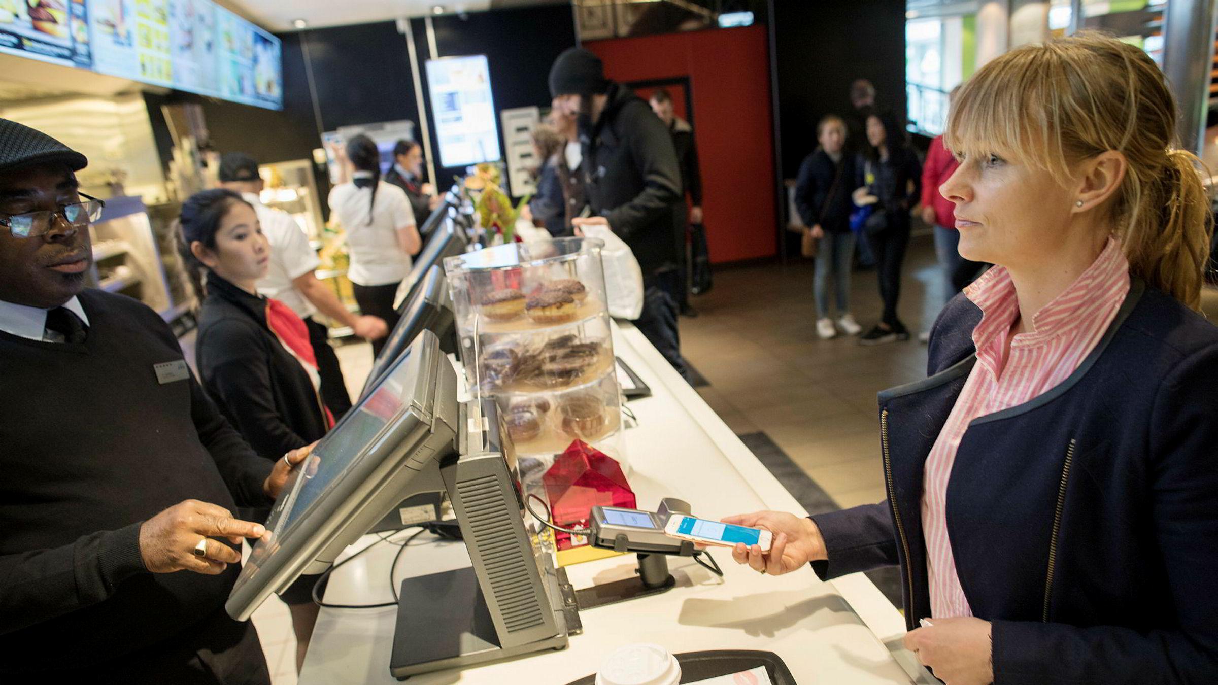 Oslo - Norge - 28.04.2017: Vipps mobil betaling - Elisabeth Haug, nestsjef i Vipps demonstrerer Vipps betaling med mobil. Her med Okeke Sampson butikksjef på Mc Donalds i Storgata. Foto: Øyvind Elvsborg