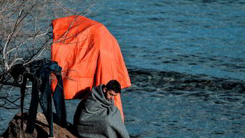 En afghansk flyktning tørker klærne sine på stranda ved Skala Sykamnias på Lesbos i Hellas, dit han kom sammen med 42 andre flyktninger natt til 6. mars.