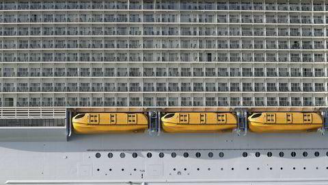 Her legger verdens største cruiseskip, «Symphony of the Seas» som tilhører Royal Caribbean Cruises, til kai 14. mars i Port Miami mens en patruljebåt kjører forbi.