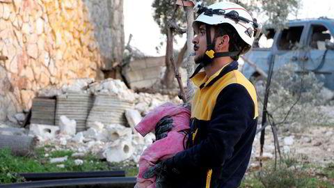 En hjelpearbeider fra sivilforsvarsgruppen De hvite hjelmene hentet torsdag formiddag ut et lite barn blant ofrene fra et russisk flyangrep i utkanten av den opprørskontrollerte landsbyen Maaret Musreen nordvest i Syria.