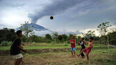 Agungs aktivitet har minsket. På bildet leker barn ubekymret for hva som kan skje hvis det skulle bli et betydelig utslipp.