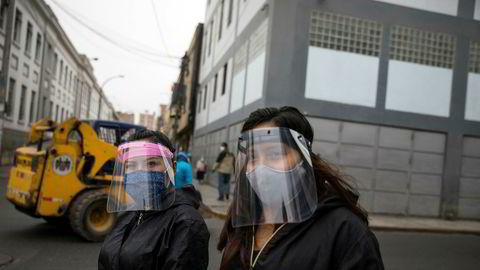 To kvinner med munnbind og visir, som har vært påbudt på offentlig transport i bykjernen i Perus hovedstad Lima. Landets økonomi har gått inn i resesjon som følge av koronapandemien.