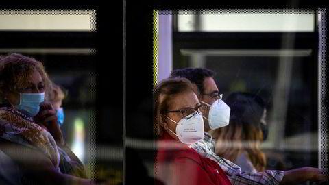 Busspassasjerer med munnbind i bydelen Vallecas i Madrid onsdag.