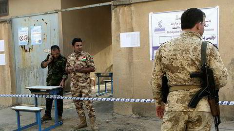 Kurdiske peshmerga-krigere holder vakt utenfor et stemmelokale under den omstridte avstemningen om kurdisk uavhengighet fra Irak.