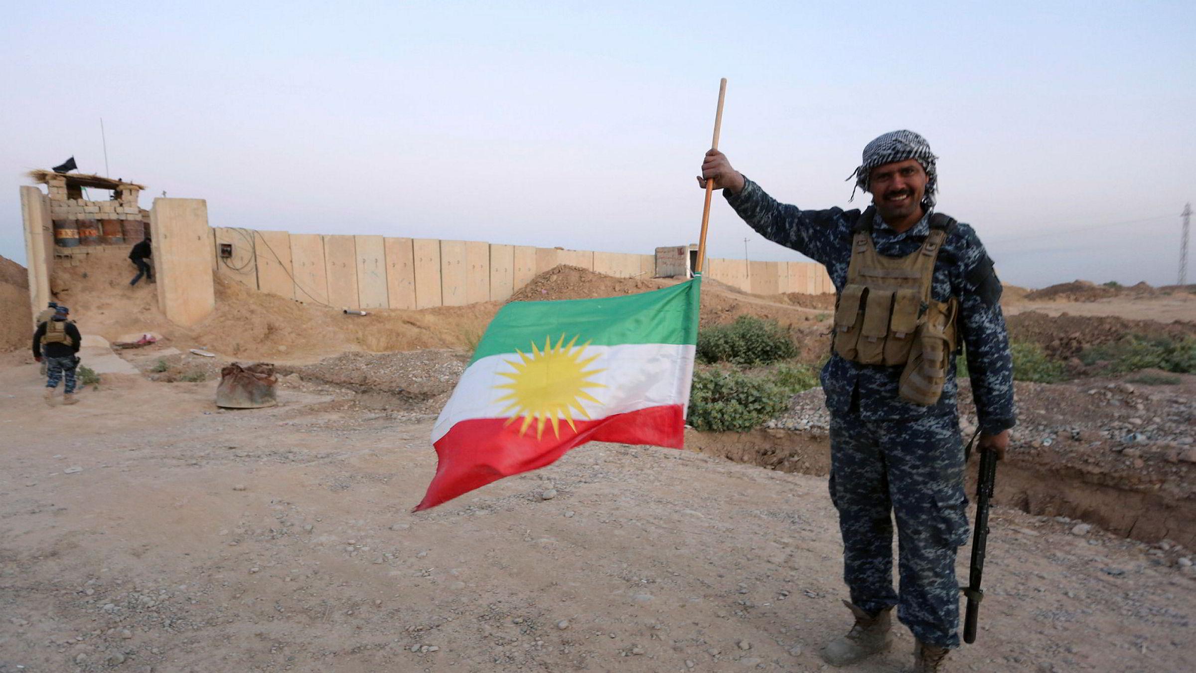 En irakisk soldat fjerner det kurdiske flagget fra oljebyen Kirkuk.
