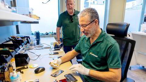 – Her i verkstedet behandler vi rundt 10 mobiltelefoner hver dag, sier serviceleder Naser Aburashid til høyre, mens daglig leder Øistein Eriksen i Release følger med i bakgrunnen.