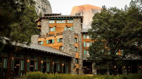 Träd, gres och stenar. Majestic Yosemite Hotel ser nesten ut som en del av naturen, der det ruver i nasjonalparken. I aftensolen skimtes fjelltoppen Half Dome, der man kan klamre seg opp i kø om klatretillatelsen er på plass.
