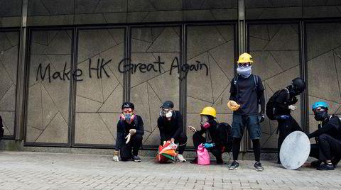 Demonstranter venter på politiet som står noen hundre meter unna. De har mursteiner og politiet tåregass. En halvtime senere skal det bryte ut store kamper. Finansmetropolen Hongkong har de siste månedene blitt en slagmark av steinkasting, tåregass og slåsskamper.