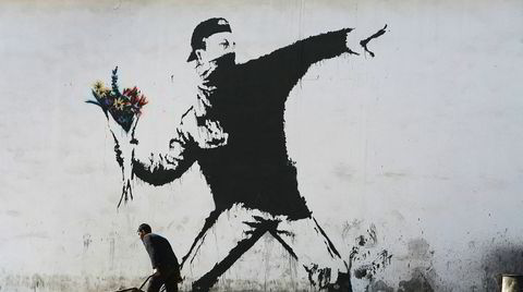 Aktivist. Banksy er elsket og hatet for sine lettfattelige politiske budskap. Dette veggmaleriet, kjent som «Flower Thrower», ble malt på en garasjevegg i Betlehem i 2005.