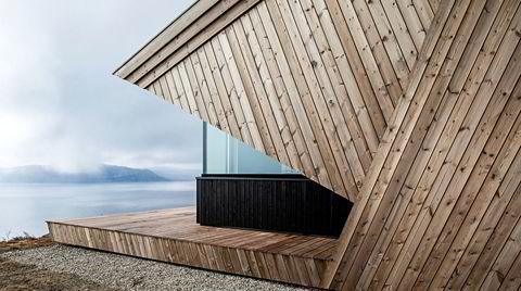 Vendt mot vann. Hytta åpner seg mot vannet og viddene i det fjerne. Overbygget omkranser hytta som en beskyttende hette.