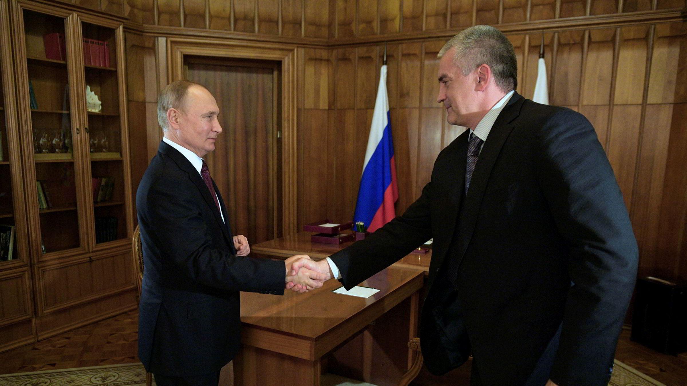 Russlands president Vladimir Putin utfører sine plikter som før. Her håndhilser han på regjeringssjefen for Krim, Sergei Aksyonov, under et møte på Krim forrige torsdag.