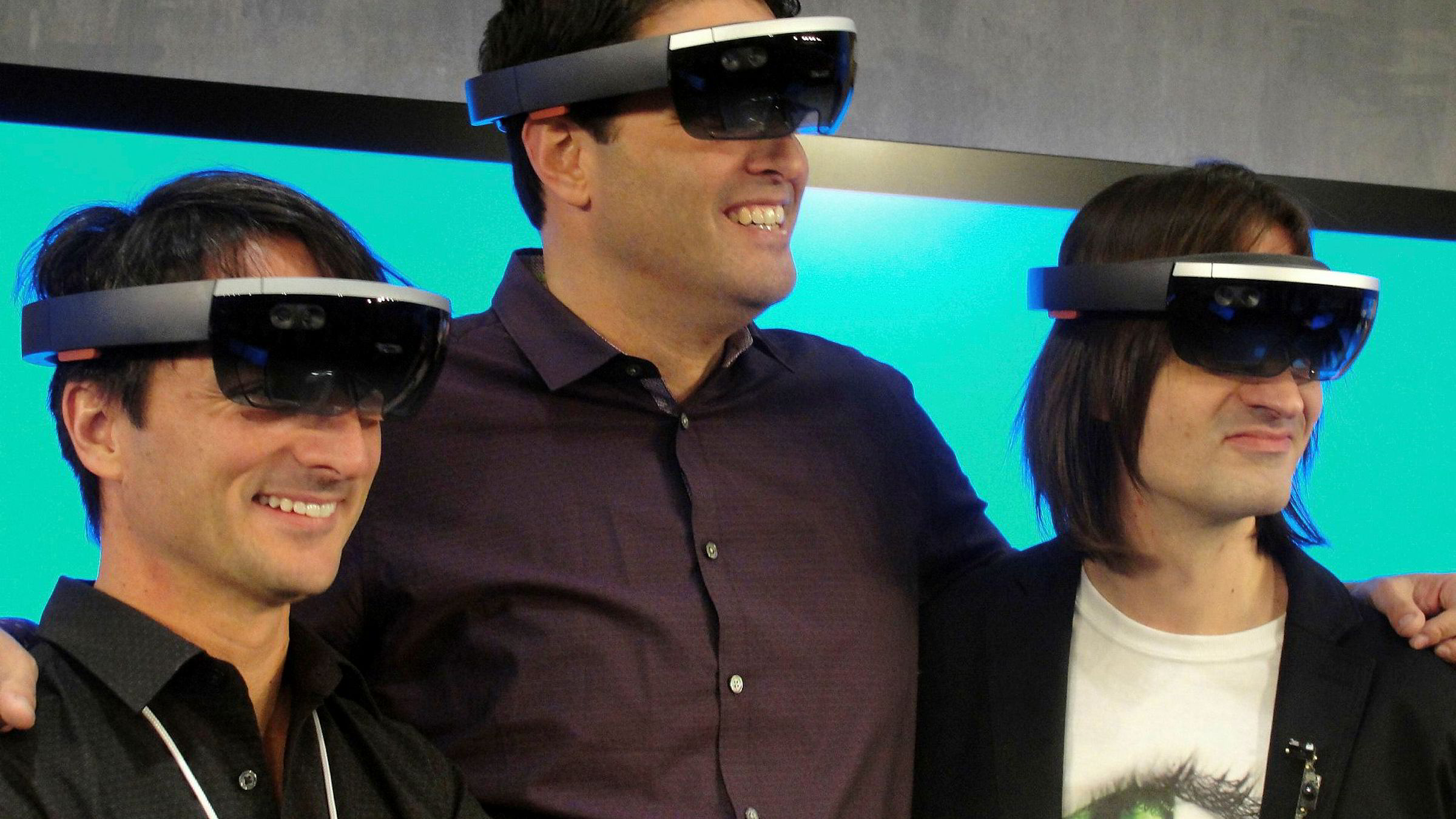 Microsoft-toppene Joe Belfiore (til venstre), Terry Myerson og Alex Kipman poserer med HoloLens-briller.