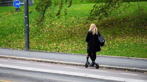 Ung dame på vei opp Henrik Ibsens gate på elektrisk sparkesykkel.