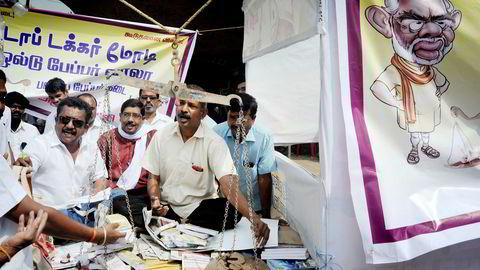 En gruppe fagforeningsmedlemmer protesterer mot endringene som gjør de største sedlene i India ugyldige. Statsminister Narendra Modi er karikert til høyre i bildet.