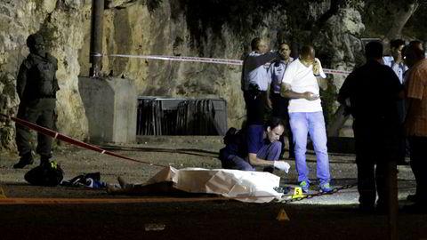 Israelsk politi står rundt en av de drepte palestinerne i Jerusalem fredag.