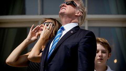President Donald Trump under solformørkelsen mandag sammen med konen Melania og sønnen Barron. Nå vil Trump forbedre forholdet til både republikanere og næringslivet gjennom skattereform. Andrew Harnik/AP/NTB scanpix