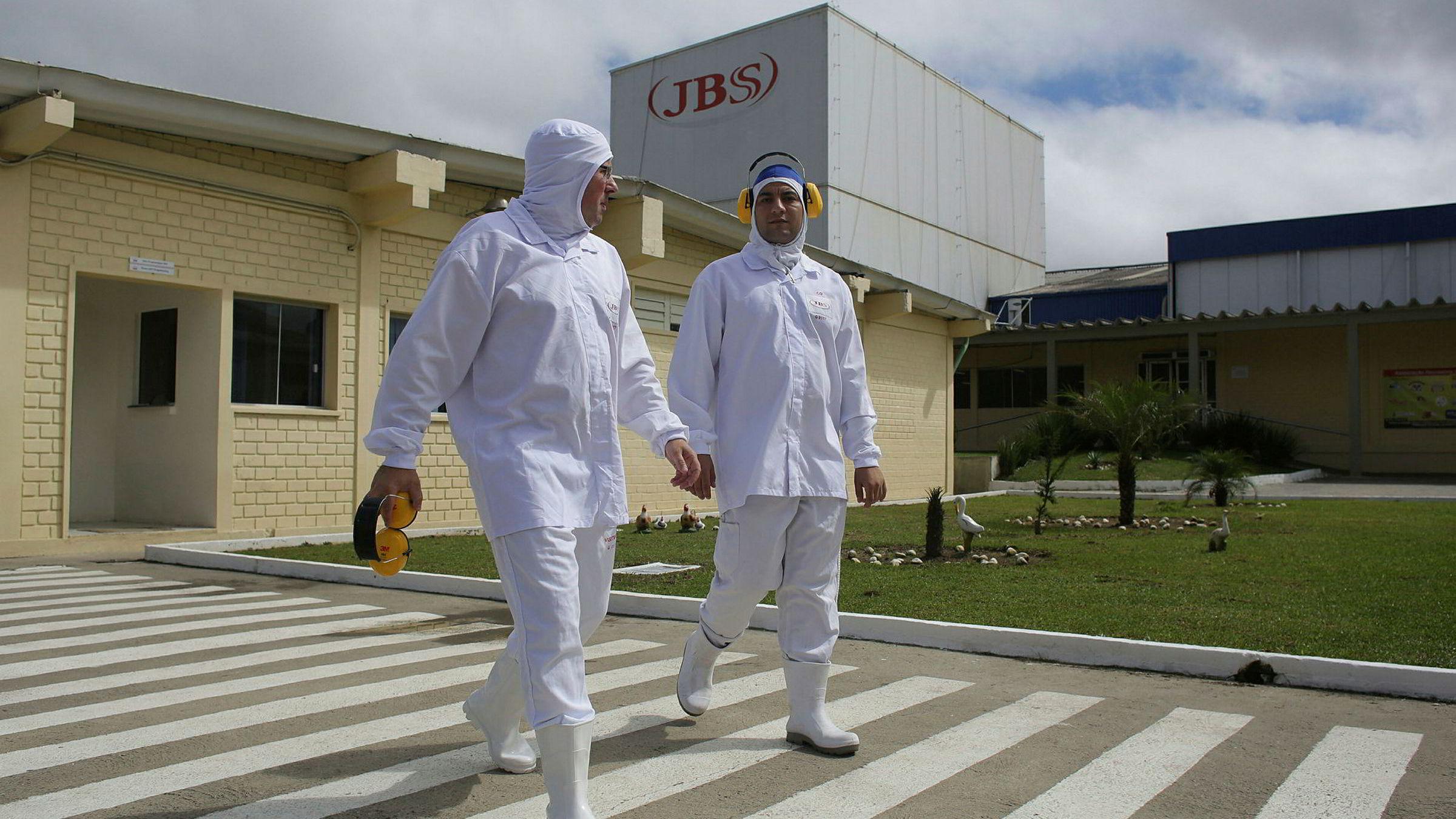 Ansatte går utenfor bygningen til kjøttpakkeren JBS i Lapa i den brasilianske staten Parana.