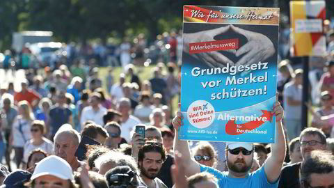 En Alternative für Deutschland-tilhenger med en «Beskytt Grunnloven fra Merkel»-plakat, under en måned før valget i Tyskland 24. september. Langt mer aggressive og pågående politiske hatkampanjer er ventet de neste dagene da partiet, ifølge Der Spiegel, planlegger å bruke tre millioner euro på politisk reklame.