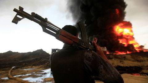 En soldat fra Iraks sikkerhetsstyrker ser utover en oljebrønn som er satt fyr på av soldater fra ekstremistgruppen som kaller seg IS 4. november. Krigføring og uroligheter i Irak har gjort at oljeproduksjonen i landet er usikker, og eksperter tviler på om landet vil opprettholde sine forpliktelser i oljekartellet Opec.