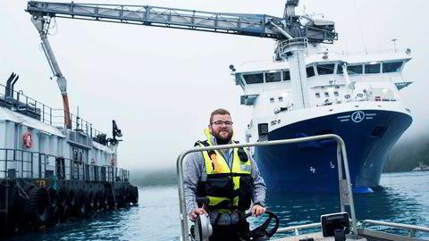 Anders Iversen er skiftleder på Wilsgård Fiskeoppdrettsanlegg i Bergsfjorden. I bakgrunnen ligger fôr-båten Artic Fjell fra selskapet Ewos.