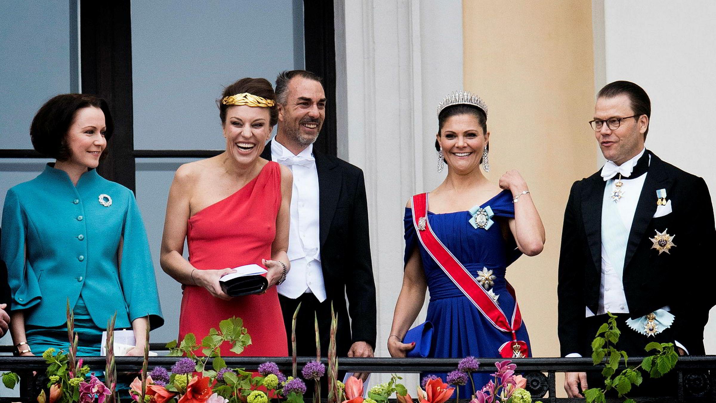 Gjester hilste ned til folket fra slottsbalkongen i anledning kongeparets 80-årsfeiring denne uken. Fra venstre: Den finske førstedamen Jenni Haukio, kronprins Haakons tremenning Desirée Kogevinas med Carlos Eugster, kronprinsesse Victoria og prins Daniel av Sverige.