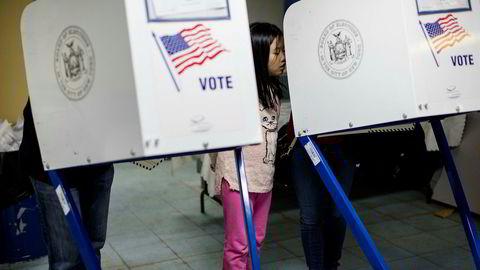 Helen Chiu (i midten) ser på at hennes foreldre Yvonne Chiu og Joseph S. Chiu avgir sine stemmer ved et valglokale i Brooklyn i New York 8. november.