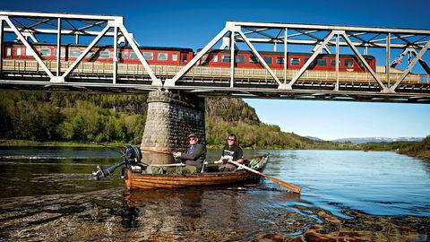 Ta toget og få fisk. På Bertnem bro utenfor Øysletta i Nord-Trøndelag finnes denne arkitektoniske merkverdigheten over den sugende, mørke kjempen Namsen: tre gamle togvogner som rett og slett er en laksecamp.