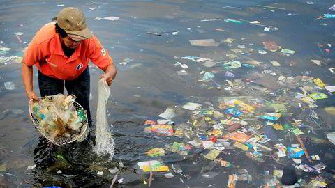 I mange asiatiske land har det hopet seg opp store plastfjell på mange deler av kysten. Bildet viser en hjelpearbeider som samler plastavfall på en strand nær Manila på Filippinene.