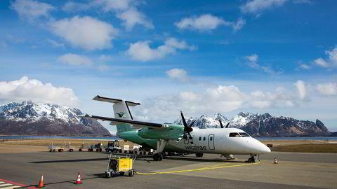 Et Widerøe-fly står på bakken. Selskapet er blant dem som er rammet kraftig av koronakrisen, samtidig som lufttransport anses som samfunnskritisk under pandemien.