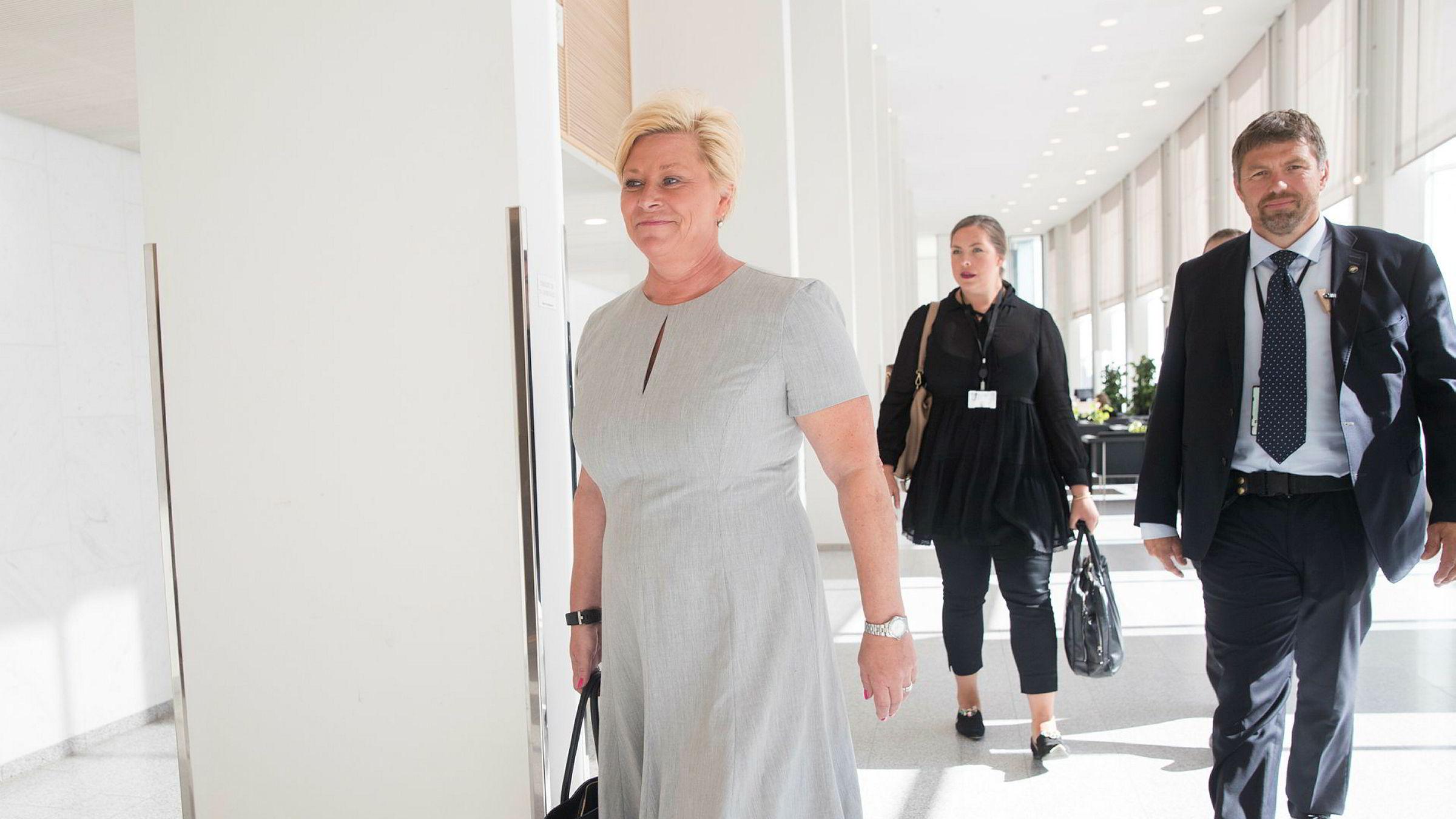 Finansminister Siv Jensen på vei inn til pressekonferansen der hun får overlevert IMFs uttalelse om norsk økonomi.