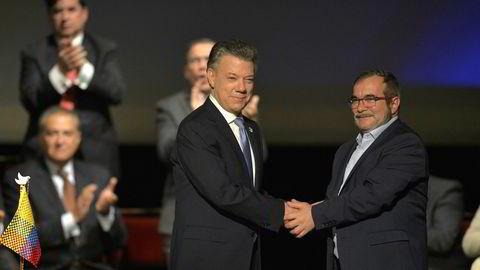 Colombias president Juan Manuel Santos (til venster) og leder av Farc-gerilliaen Timoleon Jimenez, også kjent som Timochenko, håndhilser etter den historiske fredsavtalen.