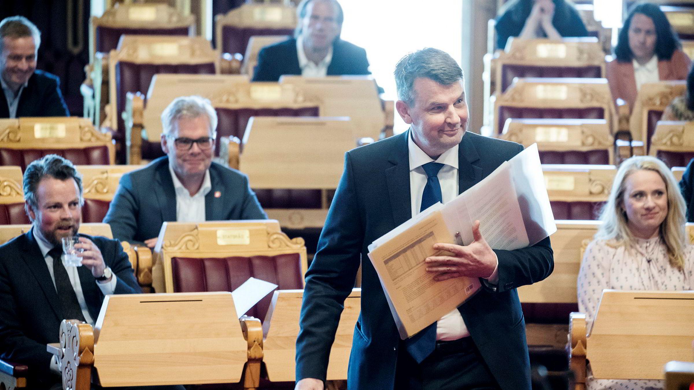 Landets nye justisminister Tor Mikkel Vara (?) balanserer permen sin på vei til talerstolen i hans første spontanspørretime på Stortinget. Til venstre er næringsminister Torbjørn Røe Isaksen. Til høyre sitter arbeidsminister Anniken Hauglie.