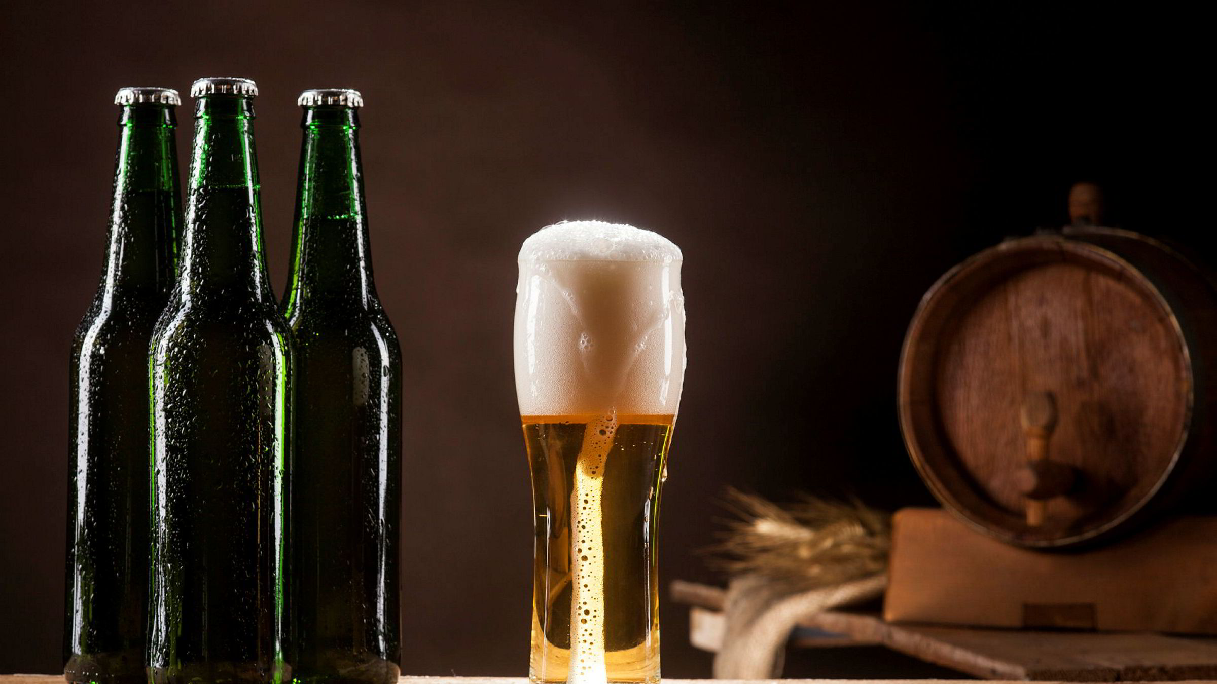 Beer barrel with beer mug and three bottles on a brown dark background. ---