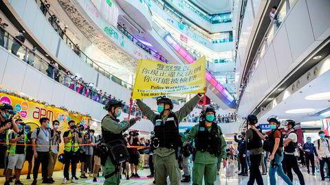 Opprørspoliti inne på et kjøpesenter i Hong Kong mandag denne uken holder opp en plakat som advarer demonstranter om at de kan bli straffeforfulgt.