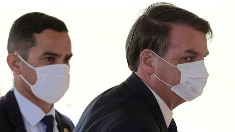 Brasils president Jair Bolsonaro på vei ut av sitt hjem Alvorada i Brasília mandag. Han fremholder at covid-19 ikke er verre en influensa og vil la folk gå til skjønnhetssalonger og på treningsstudio.