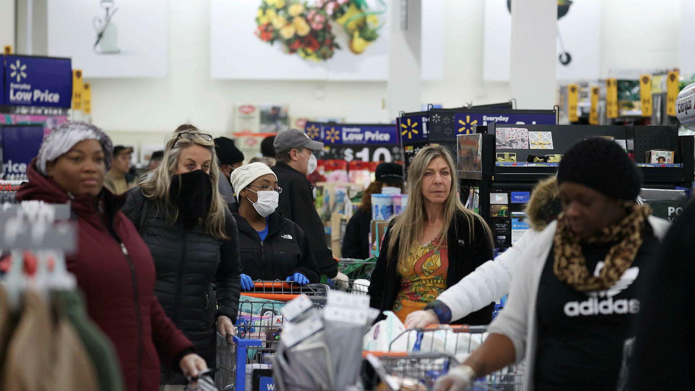 Kunder med hansker og munnbind står i kø i en Walmart-butikk i New York fredag.