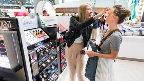Therese Myhre (38) tester ut kosmetikk på Maren Dølgaard Eid (36). Venninnene, som skal til Amsterdam, handler kosmetikk på Gardermoen, men regner ikke med at de sparer så mye.