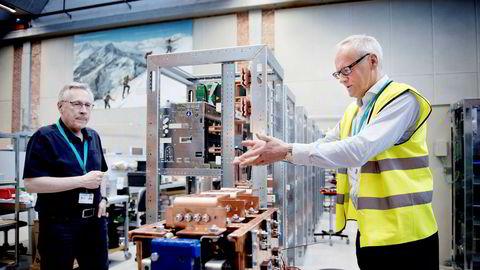 Salgsdirektør Odd Moen (til høyre) viser sammen med Alf Olav Valen enhetene som skal lade batteriene som selskapet skal utvikle.