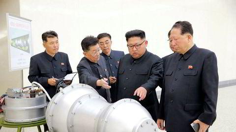Dette bildet, som er sendt ut av Nord-Koreas statlige nyhetsbyrå, viser angivelig Kim Jong-un (nummer fire fra venstre) med kjernevåpeneksperter.